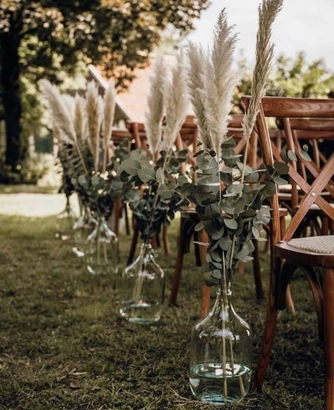 Vazen langs ceremoniestoelen met pampusgras